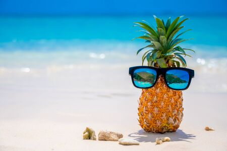 Glasses pineapples are located on the beach by the sea in the hot sun, setting the concept for summer.