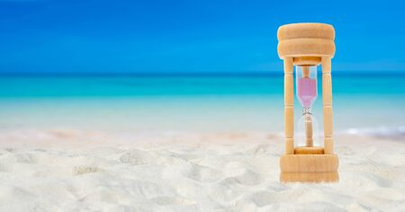 Hourglass set on a white sand background sea background, time concept Imagens