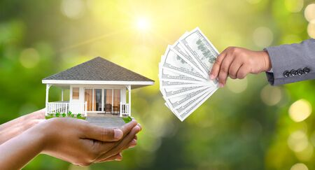 The hands of a businessman hold money and the other hand holds a house. The idea of saving money to buy a house