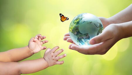 Adults are sending the world to babies. Concept day earth Save the world save environment The world is in the grass of the green bokeh background 版權商用圖片