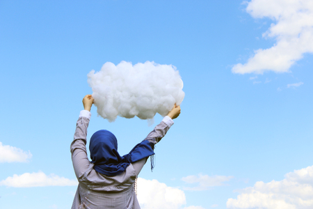 yashmak: Muslim girl holding a cloud of cotton wool against the background of a summer Stock Photo