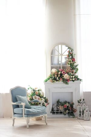 Bright room, fireplace and blue armchair. A lot of flowers and candles. Stock Photo