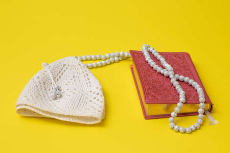 Pink Quran and white muslim rosary and white skullcap on a yellow background