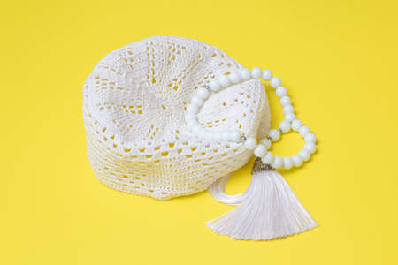 Muslim skullcap and white rosary on a yellow background