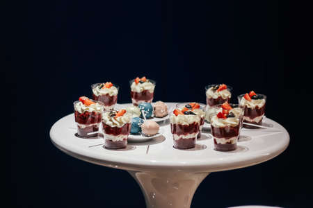 Desserts with whipped cream and strawberries on a white table. Glamorous style