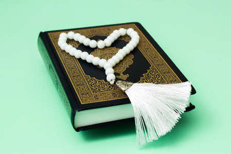 Quran and white muslim rosary in the shape of a heart on a green background