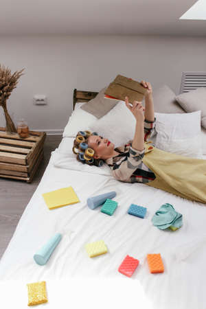 The girl in the curlers lies in bed. Near different sponges and pulverizer Zdjęcie Seryjne