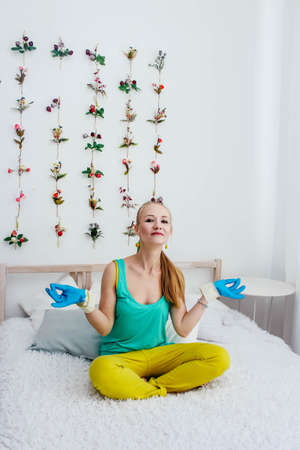 Blonde girl in gloves on the bed