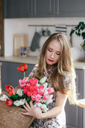 Blonde girl with a basket of tulips in the kitchen