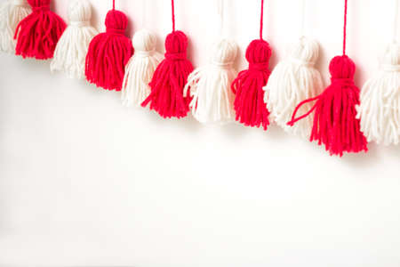 brushes from yarn of red and white color on a white background. DIY yarn brushes. Garland Garland of yarn. Pampushki from yarn. Children's creativity. Close plan Banque d'images