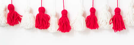 brushes from yarn of red and white color on a white background. DIY yarn brushes. Garland Garland of yarn. Pampushki from yarn. Children's creativity. Close plan.