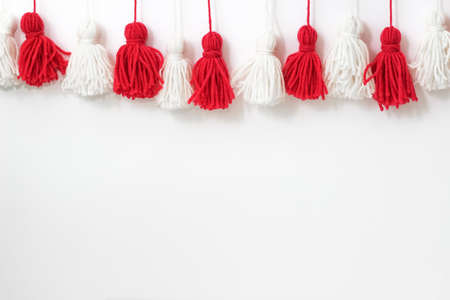 brushes from yarn of red and white color on a white background. Space for copy space. DIY yarn brushes. Garland Garland of yarn. Pampushki from yarn. Children's creativity