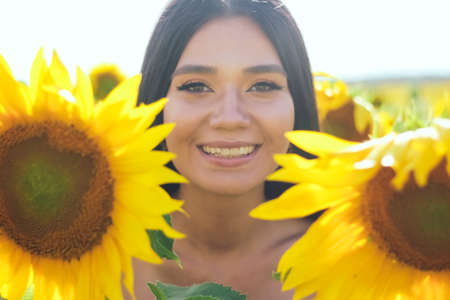 Beautiful brunette woman in a white top on the field with sunflowers. Yellow sunflowers. Close plan. Standard-Bild