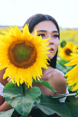 Beautiful brunette woman in a white top on the field with sunflowers. Yellow sunflowers. Close plan.