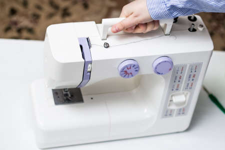 The girl holds the handle of a sewing machine. White sewing machine.
