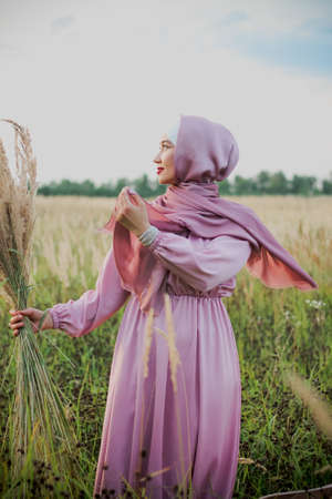 Muslim woman in a pink hijab on a field with wheat