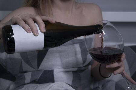 beautiful slender half-naked girl pours red wine from a bottle without a label into a huge glass and in bed - horizontal photo