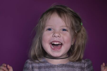 portrait of happy a three year old blond girl with blue eyes on a pink background Stock fotó