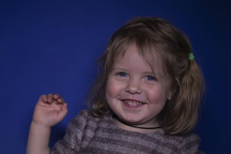 portrait of happy a three year old blond girl with blue eyes on a blue background Stock fotó