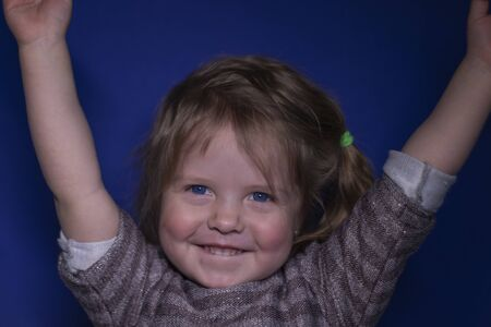 portrait of happy a three year old blond girl with blue eyes on a blue background - hands up