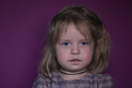 portrait of a three year old blond girl with blue eyes on a pink background