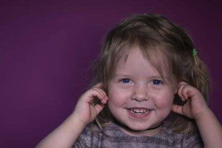 emotional portrait of happy a three year old blond girl with blue eyes on a pink background Stock fotó