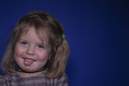 emotional portrait of happy a three year old blond girl with blue eyes showing her tongue on a blue background Stock fotó