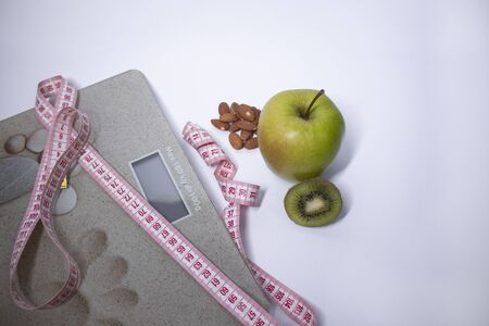 Red measuring tape, apple, kiwi and almonds near beige bathroom scales. Diet and Healthy life, loss weight, sport concept. Top view. Copy space. Isolated. White background