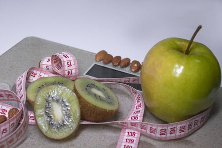 Red measuring tape, apple, kiwi and almonds on beige bathroom scales. Diet and Healthy life, loss weight, sport concept. Copy space. Isolated. White background