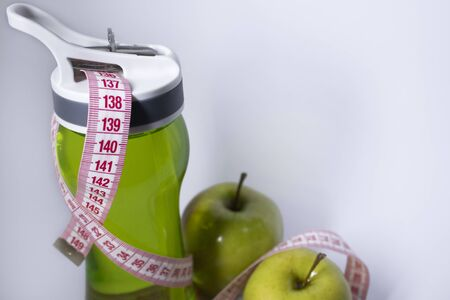 Red measuring tape over green sport bottle and green apple. Diet and Healthy life, loss weight, sport concept. Top view. Copy space. Isolated. White background. High quality photo