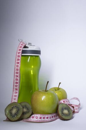 Red measuring tape over green sport bottle, apple and kiwi. Diet and Healthy life, loss weight, sport concept. Top view. Copy space. Isolated. White background. High quality photo Stock Photo