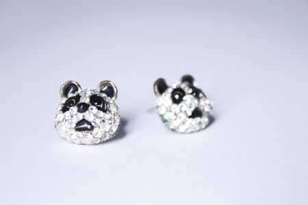 Silver earrings panda-shaped. jewelry and accessories concept. Isolated, copy space. Macro Shot. High quality photo 写真素材