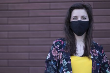 Attractive young brunette woman in yellow t-shirt and flowery shorts costume. In medical black face mask. brown wall background. modern reality. covid-19 concept. copy space. High quality photo