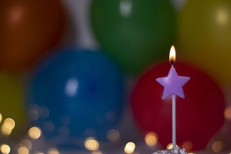 festive purple star-shaped candle. On the background of multi-colored balloons and lights. party, birthday concept. Copy space. . High quality photo Stockfoto