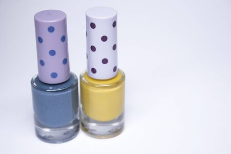 Bottles with blue and yellow nail polish on white background. nail lacquer. Nail manicure concept. Isolated, copy space.