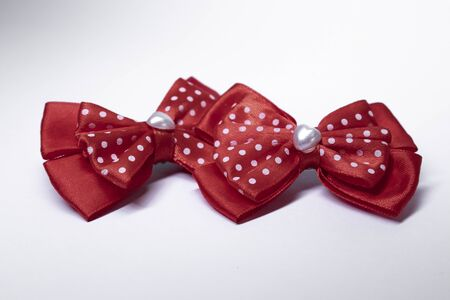two red polka dot bow hairpins with a heart in the middle. accessories concept. Isolated, copy space. Macro Shot. High quality photo 版權商用圖片
