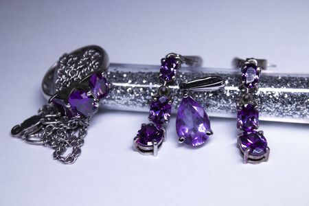Expensive set of silver womens jewelry with violet stones - ring, pendant and earrings. Isolated, copy space. Macro Shot 版權商用圖片