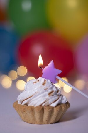 festive cupcake with a purple star-shaped candle. On the background of red gift box with a pink ribbon, multi-colored balloons and lights. party, birthday concept. Copy space. . High quality photo Stok Fotoğraf