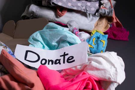 Donate sign handwritten with black letters. A box with clothes and a pile of clothes nearby on a grey table.clothes donation concept. copy space. High quality photo