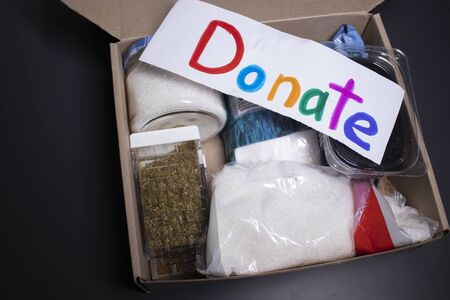 donation sign handwritten with multicoloured letters. A box with food supplies on a grey table. food donation concept. copy space. High quality photo
