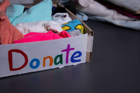 Donate sign handwritten with multicoloured letters. A box with clothes and a pile of clothes nearby on a grey table.clothes donation concept. copy space. High quality photo