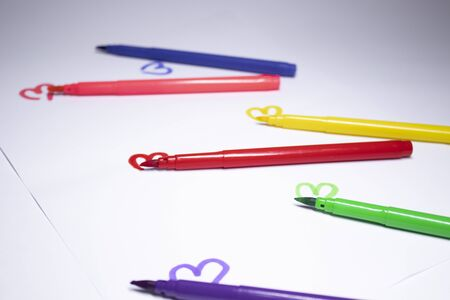 multicoloured felt-tip pen with a painted heart next to it. stationery concept. copy space. isolated. High quality photo
