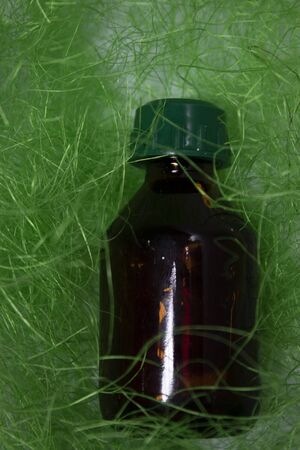 little liquid bottle with no label in green grass-like thing. body care and beauty concept. Copy space. High quality photo