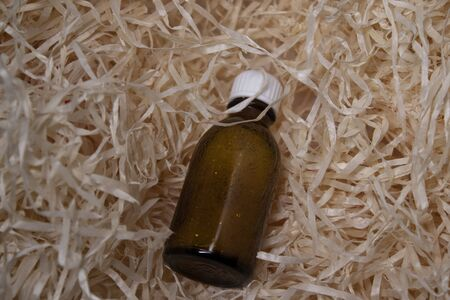 empty brown little bottle with no label in dried grass. body care and beauty concept. Copy space. . High quality photo