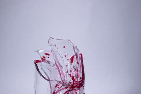 drops of red liquid - blood - on the fragments of a broken glass in a broken glass on a white background. Isolated. Copy space. pain concept. High quality photo