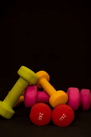 Bright pink, green, red and yellow small dumbbells on a black background. Sport concept. High quality photo