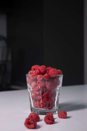 transparent glass with raspberries on white table in gray kitchen. High quality photo