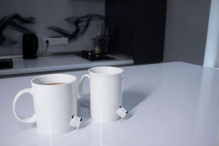 two white cups with tea and sticking out tea bags on a white table in a gray kitchen. High quality photo 스톡 콘텐츠