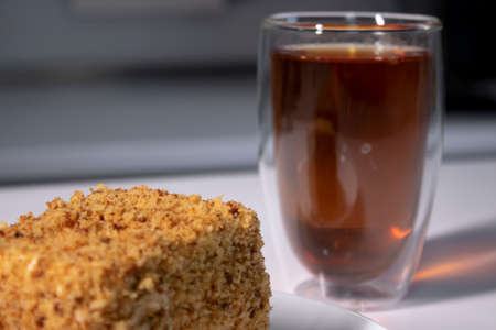 cup of tea in a double-botoom glass and piece of cake on white table in gray kitchen. High quality photo