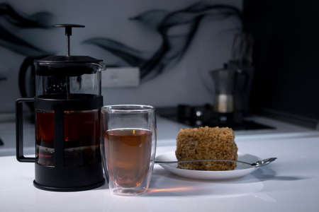 cup of tea in a double-botoom glass, french-press teapot and piece of cake on white table in gray kitchen. High quality photo